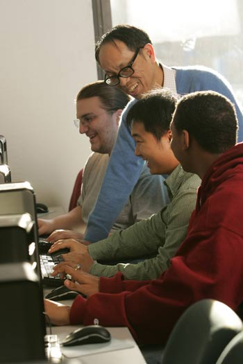Frank Hsu, Ph.D., works on a computational problem with computer science students (from left to right) junior Chris Belsole, graduate student Qian Ma, and junior Heyward Starks. Photo by Bruce Gilbert