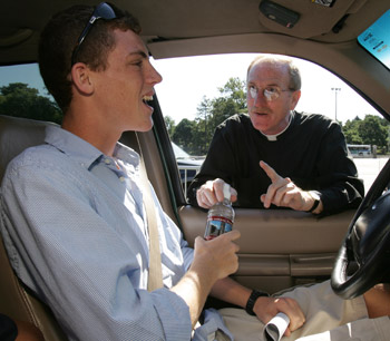 Joseph M. McShane, S.J., president of Fordham University, dispenses Fordham bottled water and some advice to freshman Andrew Brown as he arrives on the Rose Hill campus on Sept. 2.  Photo by Bruce Gilbert