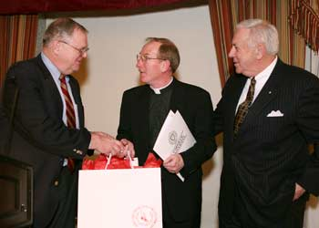 Joseph M. McShane, S.J., is greeted after his talk at the New York Athletic Club by club vice president Robert Geary (left) and former president Al Green (right), chairman of the NYAC Forum Committee. Photo by Michael Dames