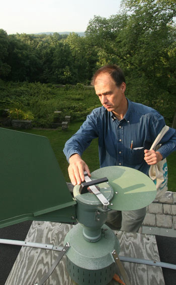 Guy Robinson, Ph.D., lecturer at Fordham, secures a sampling device on the roof of the Calder Center. The device traps pollen in the air, which allows Robinson to issue a count that is made available to the public.  Photo by Bruce Gilbert