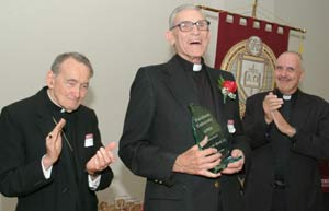 Vincent M. Novak, S.J., one of the founders of the Graduate School of Religion, receives a special award as Avery Cardinal Dulles, S.J., (left) and the Rev. Anthony J. Ciorra, Ph.D., look on. Photo by Chris Taggart