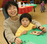 "CBA professor Sarah J. Wu helps her daughter Victoria, age 2, make a ""reindeer bag"" at the annual Christmas party at the McGinley Ballroom.  Photo by Michael Dames"