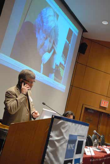"""Dennis Burke, former campaign manager for Doris """"Granny D"""" Haddock, speaks with Haddock via cell phone while a still image is projected behind him.  Photo by Chris Taggart"""