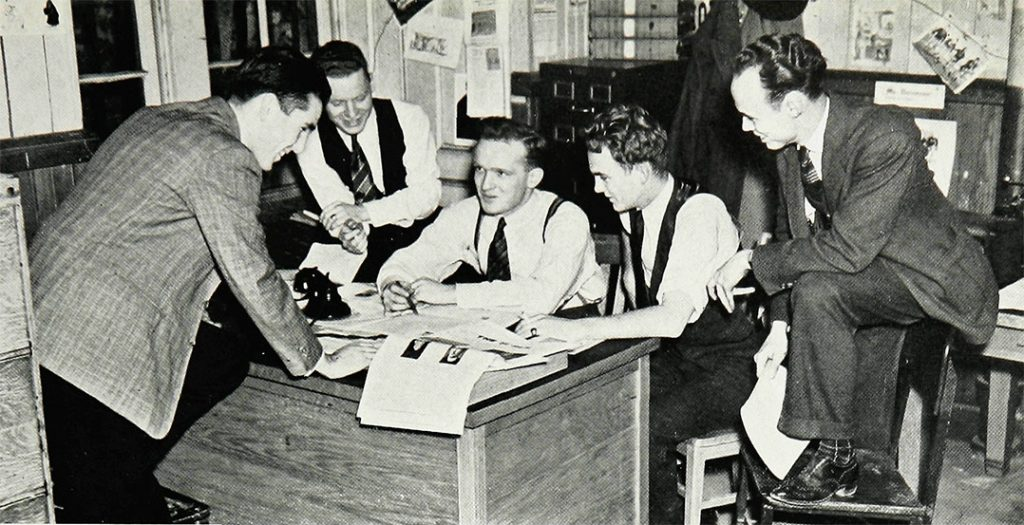 Editor-in-Chief Donovan (center) holds court with his fellow newsmen in the offices of The Ram.