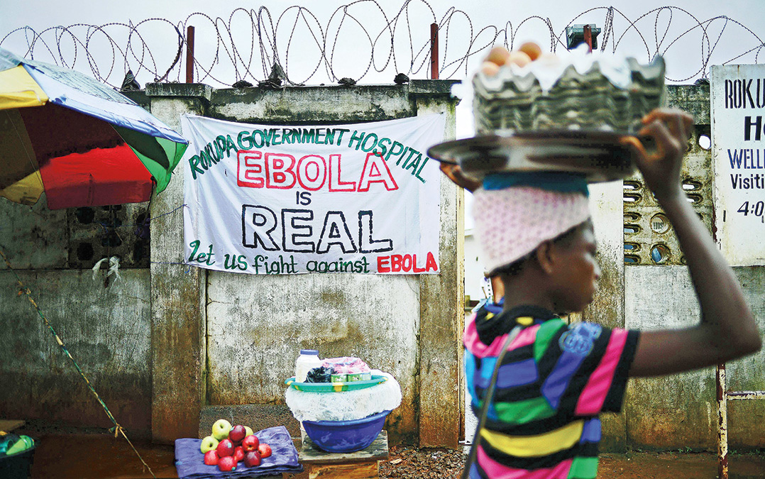A young woman walks past an Ebola warning sign outside a government hospital in Freetown, Sierra Leone, in August 2014. Carl De Souza/AFP/Getty Images