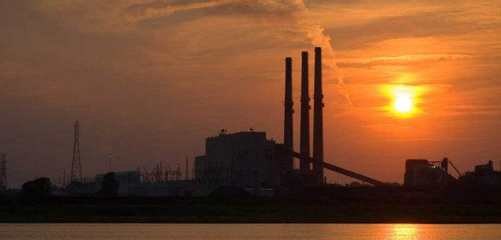 a coal power plant in an orange sky at sunset