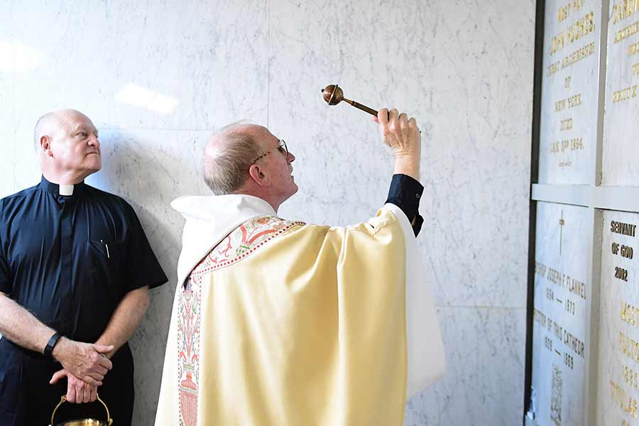 Father McShane blesses the plaque of Archbishop Hughes.