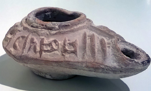 "Oil lamp inscribed ""The light of Christ shines for all,"" Byzantine, ca. 5th century C.E. Terracotta, l (from handle to nozzle): 3¼ in. (8.25 cm), from the Fordham Museum of Greek, Etruscan, and Roman Art"