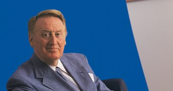 Fordham alumnus Vin Scully, the legendary sportscaster and Voice of the Dodgers, wearing a blue sport coat and sitting in front of a blue background.