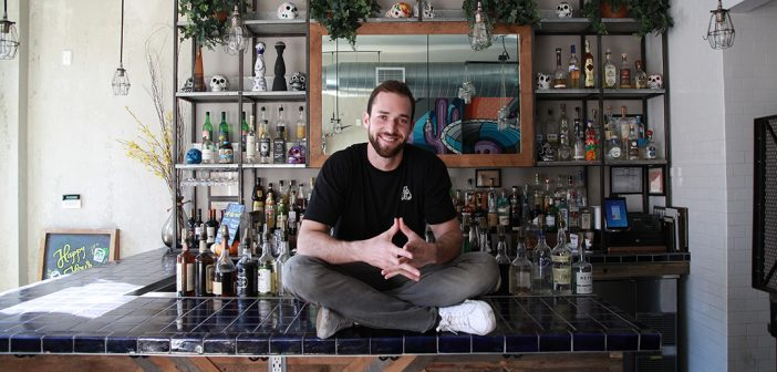 Fordham graduate Matt Trebek sits on the bar at Oso, the Mexican restaurant he opened in 2016 in the Harlem's Hamilton Heights neighborhood.