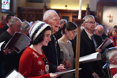 Bernadette Haig and Richard Hoar, S.J., get in the holiday spirit, joining the choirs in song during the annual Christmas Festival of Lessons and Carols at the University Church.