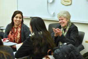 Sandra Turner and Mentoring Latinas mentor Kathryn Madigan talk with mentees during a holiday party at Fordham College at Rose Hill. Photo by Dana Maxson.