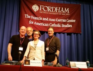 Thomas Kelly, Tom Fontana, Karin Coonrod, and panel moderator George Drance, S.J.  pose for a picture from the stage.