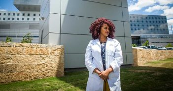 Carli Mendoza in front of Parkland Hospital, part of the UT Southwestern system where she is completing her residency
