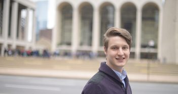 Alex McCauley standing in front of Lincoln Center, with hte Metropolitan Opera behind him.