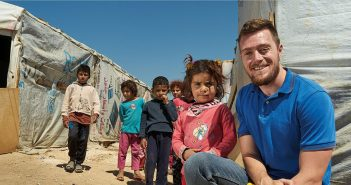 Catholic Relief Services worker and Fordham graduate Sean Kenney poses with Syrian refugee children living in Lebanon's Bekaa Valley