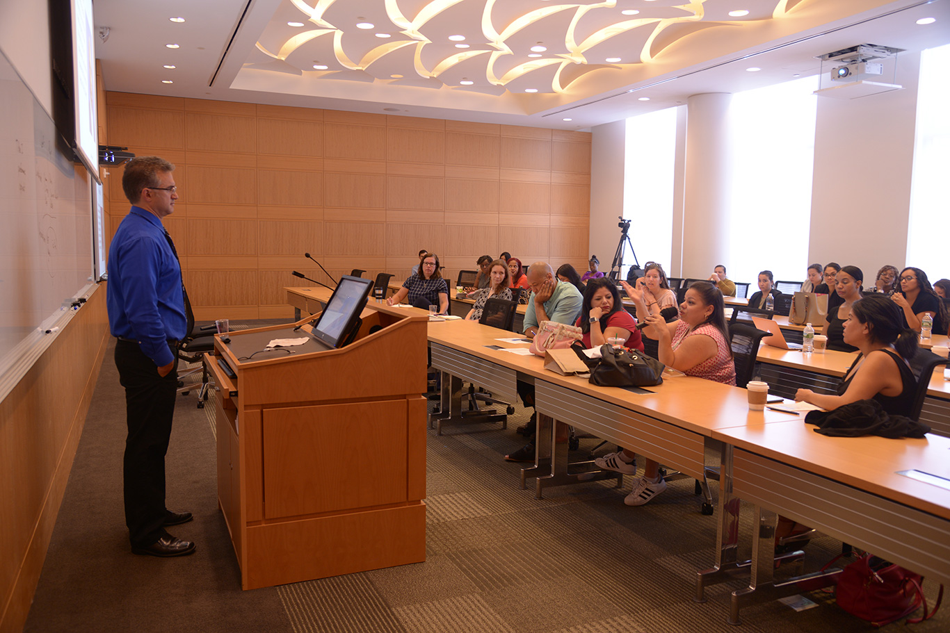 Nicholas Tampio answers questions from attendees seated in a conferance room at Fordham Law School