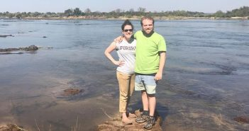 Fordham alumni Whitney Rog and her husband, Justin Lucas, stand on a rock in a river in Zambia, where they spent some time this summer assisting residents in establishing a small school for children in a rural village in Livingstone.