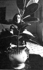 Lori O'Connor sits behind her tall rubber plant.