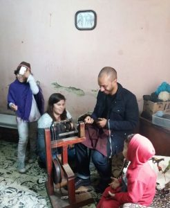 MBA student Dominic Swain, whose team served as consultants to Azul Solidario, spins yarn from sheep's wool with help from an Argentinian weaver