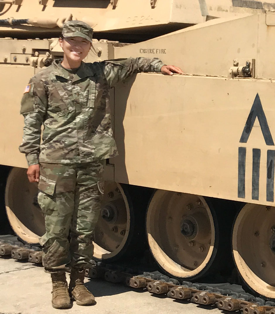 Esther Kim, a 2016 Fordham graduate and one of the first women allowed into combat roles in the U.S. military, is shown dressed in Army fatigues and standing next to a tank.