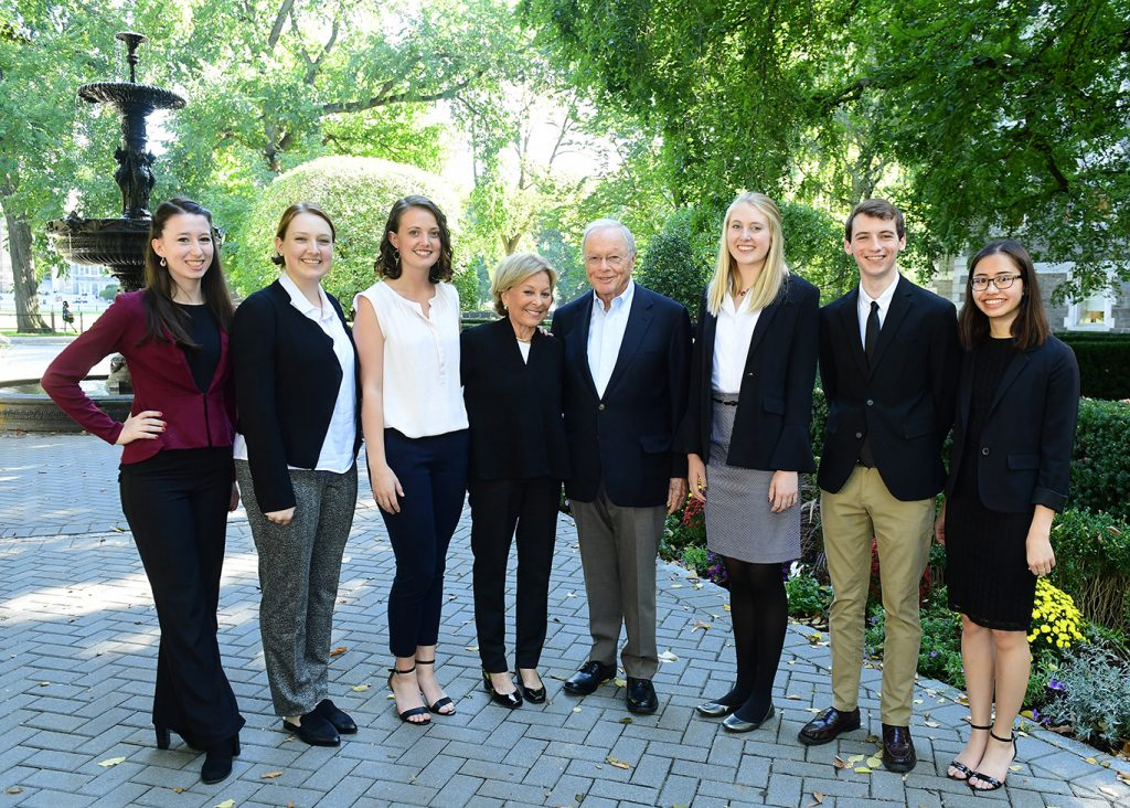 Rose O'Neill, Natalie Grammer, Lucie Taylor, Maurice J. (Mo) Cunniffe, FCRH '54, Carolyn Dursi Cunniffe, Ph.D., GSAS '71, Erin O'Rourk, Andrew Souther, and Ashley Conde pose for a picture in front of the fountain on the Rose Hill campus