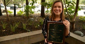 Shannon Hirrel Quinn holds the plaque honoring Fordham's participation in the St. Patrick's Day Parade