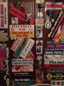 Vintage stickers cover the bathroom door.