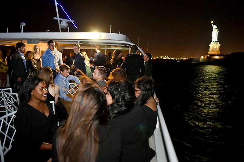 Guests mingle on the top deck as Fordham's 2017 Young Alumni Yacht Cruise passes within view of the Statue of Liberty.