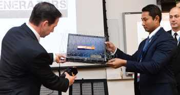 "Damianos Pinou activates an electromagnetic pulse generator under a laptop wrapped in a metal mesh ""Faraday cage"" held by Rien Chy, as Thaier Hayajneh looks on."
