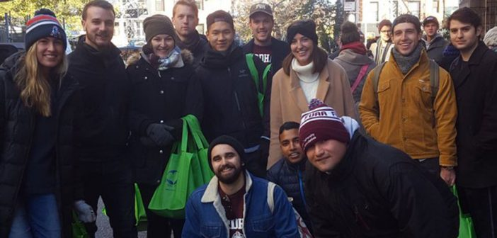 Fordham young alumni handing out care bags at a volunteer event