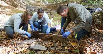 Elle Barnes, Erin Carter and Dan Khienenson lift up boards to find red salamanders on the grounds of the Calder Center