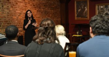 "Fordham theology professor Brenna Moore delivers a ""Faith on Tap"" talk to a group of Fordham alumni in the backroom of a Midtown Manhattan bar"