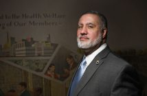 """Fordham Law grad Mark Torres, general counsel for the Teamsters Union Local 810, stands in front of a New Deal-era, pro-union mural created by Auriel Bessemer. The text on the mural reads in part, """"Dedicated to the Health, Welfare and Well-being of Our Members."""""""