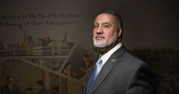 "Fordham Law grad Mark Torres, general counsel for the Teamsters Union Local 810, stands in front of a New Deal-era, pro-union mural created by Auriel Bessemer. The text on the mural reads in part, ""Dedicated to the Health, Welfare and Well-being of Our Members."""
