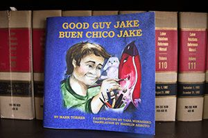 A copy of Mark Torres' children's book, Good Guy Jake aka Buen Chico Jake, stands out on a shelf of legal books in his Long Island City office.