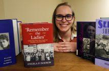 Bookshelf of Suffragette books with grad student