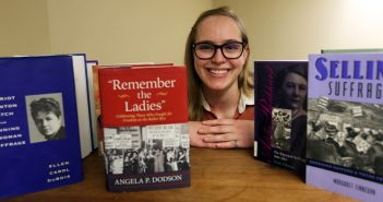 Bookshelf of Suffragette books with grad student