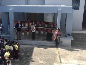 Aida Nevárez-La Torre, Ed.D., and Jacqueline Bocachica González, Ed.D. present boxes of school supplies to the students of Escuela Julio Alvarado Tricoche.