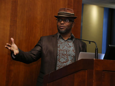 Pulitzer Prize winner Tyehimba Jess holds his book Olio at the podium at Poets Out Loud reading on April 11
