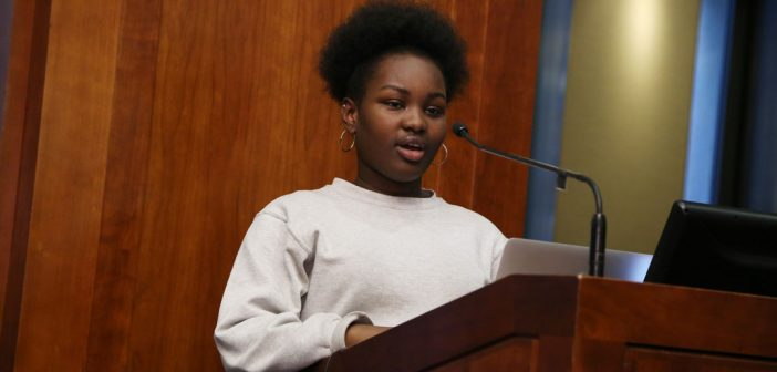 High schooler Laurynn Laurore reads poetry at the podium at Poets Out Loud reading on April 11