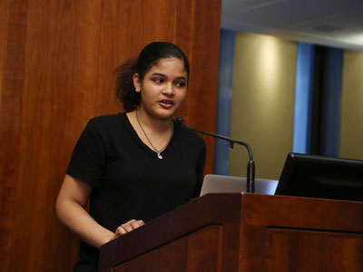 High schooler Deliana Rosario reads her poetry at the podium at Poets Out Loud reading on April 11