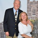 Alumni couple pose for a picture in front of a cut out of Keating Hall
