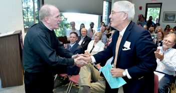 Joseph M. McShane shakes hands with Peter Calder at the 50th anniversary celebration of the Calder Center