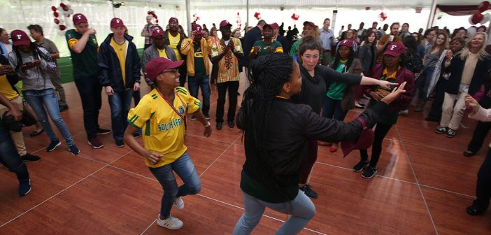Fordham staff dance with South African exchange students under a tent at Rose Hill.