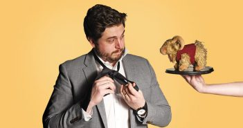 Saturday Night Live writer (and Fordham graduate) Streeter Seidell puts on a necktie and looks at a stuffed toy Fordham Ram on a silver platter