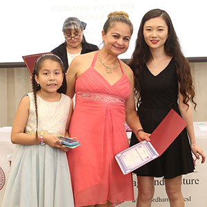 An ESL student and her daugher, bith in fancy pastel dresses, receive a certificate from her ESL teacher
