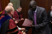 Father McShane congratulates IDHA graduate Deng Khoryoam as he receives his diploma.