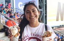 Female international student with black hair holding two ice cream cones at a Mets game