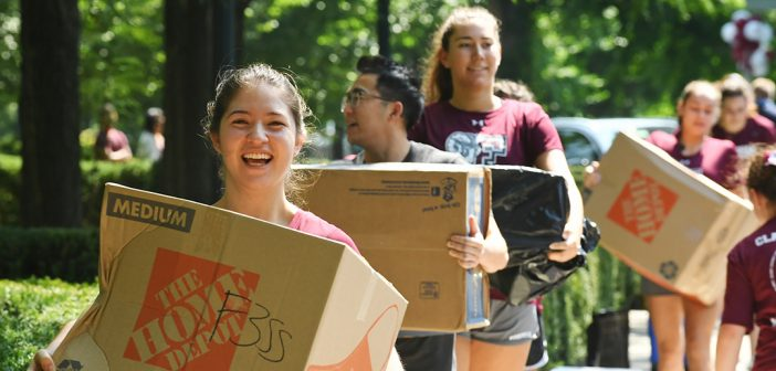 Student volunteers carry boxes on the Rose Hill campus